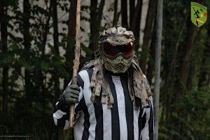 Referee mit Maske und Stock in der Hand